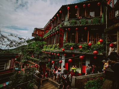 A building in Jiufen, Taiwan covered with red lanterns and green plants