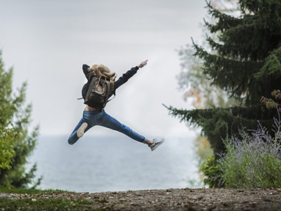 A person jumping in the air in front of a lake
