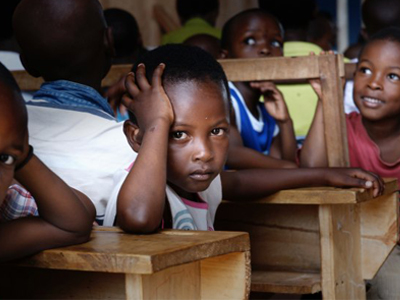 A child turning away from the front of the classroom and facing the camera