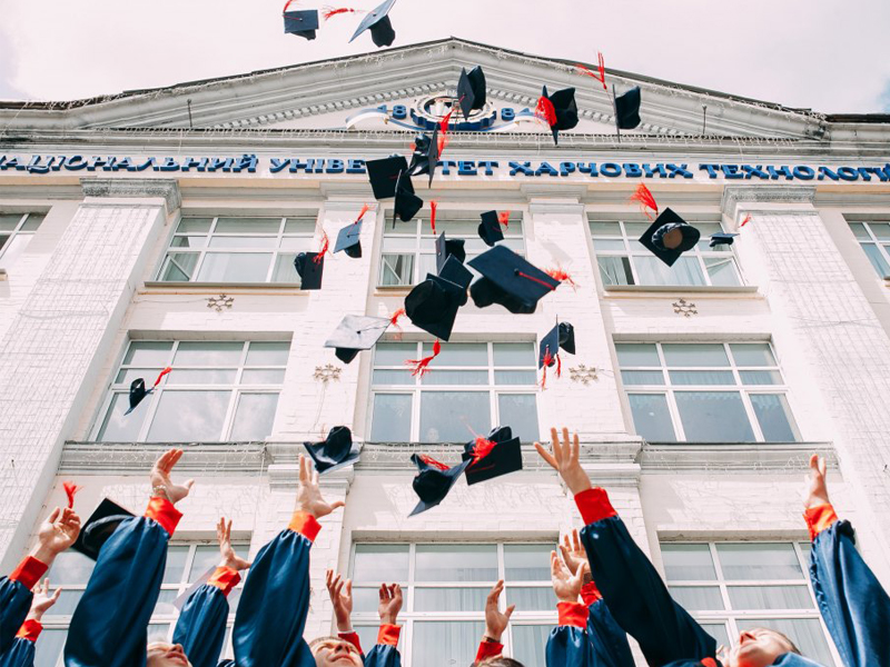 Graduates throwing their caps into the air outside a university