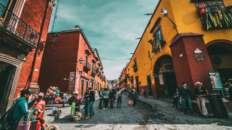 Street sellers and tourists on a colourful street in Mexico