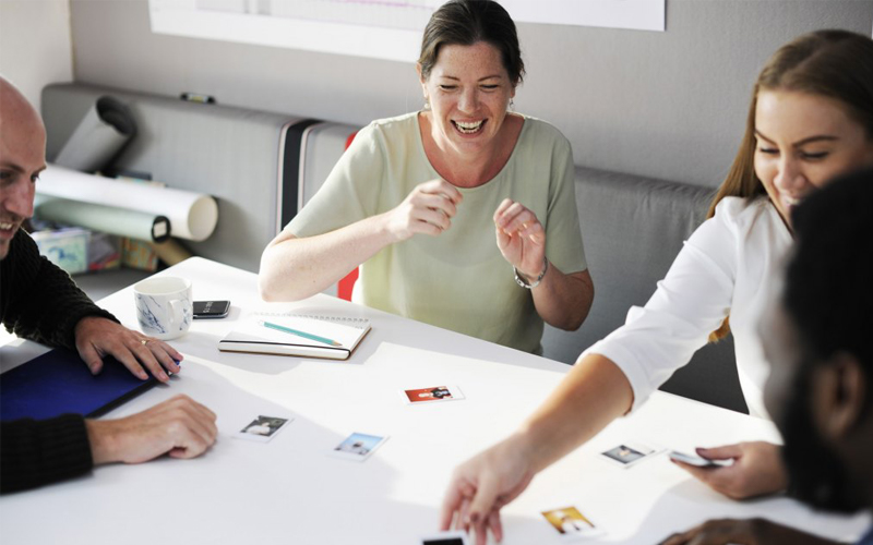 A group of adults playing a picture card game during a lesson
