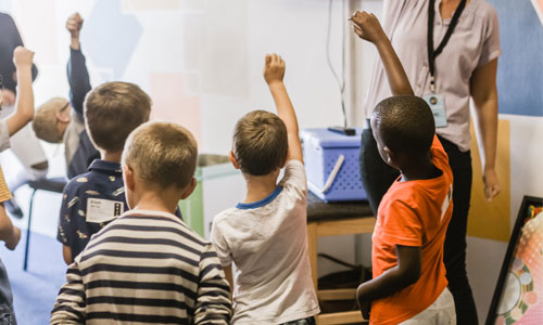Young students putting their hands up
