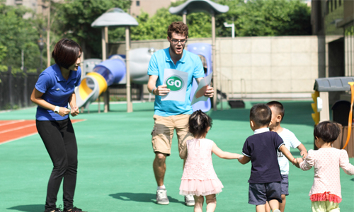 Two teachers playing a game with young children outside