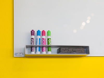 Colourful whiteboard markers in front of a whiteboard