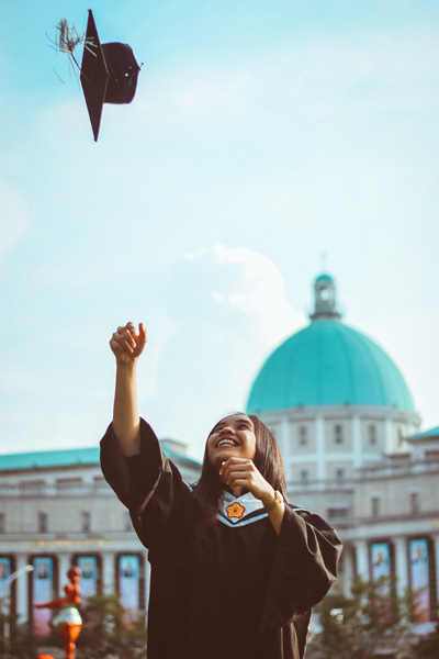 A person throwing a graduation cap in the air