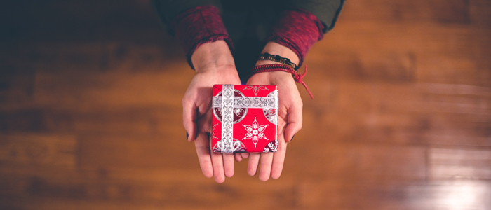 A person holding out a red gift