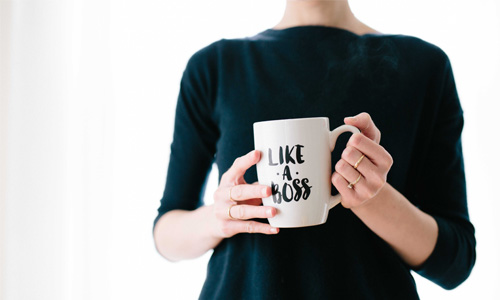 A person holding a mug with 'like a boss' written on the side