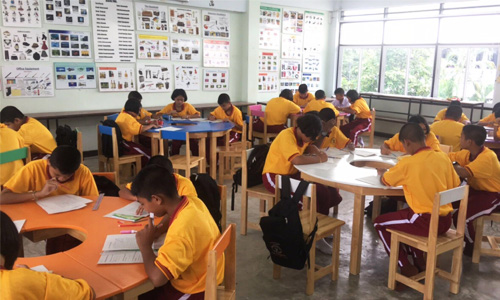 Children writing at desks in a classroom