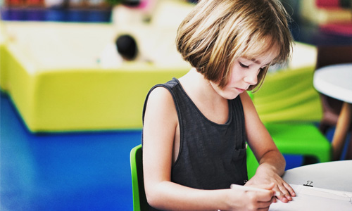 A child writing at a desk