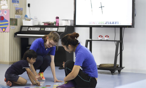 Teachers playing a writing game with a young student