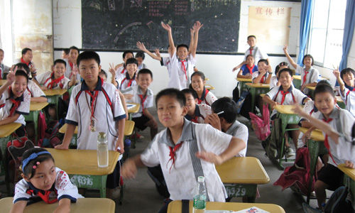 Children in a classroom waving at the camera