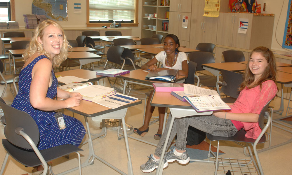 A teacher working with two students
