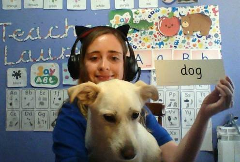 An online teacher with a dog and the word 'dog' on a flashcard