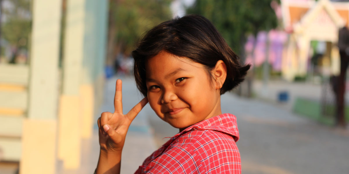 A child smiling at the camera and doing the 'peace' sign