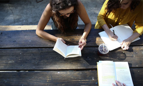 Three people studying at a picnic table