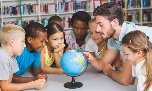 A teacher showing children places on a globe