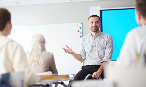 A teacher speaking at the front of the class