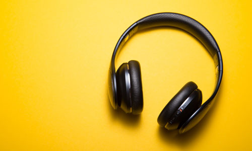 A pair of headphones on a yellow background
