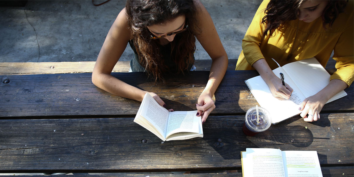 People reading books at a park table