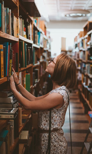 A person looking at books in a library