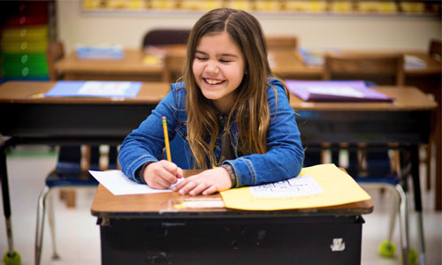 A child smiling and writing at a desk