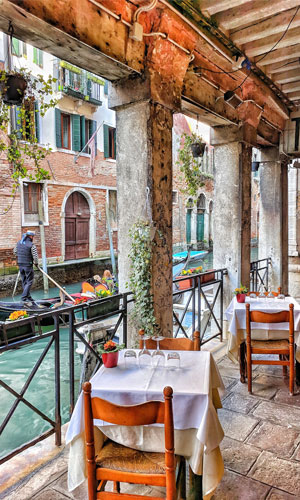 A restaurant by a canal in Venice, Italy