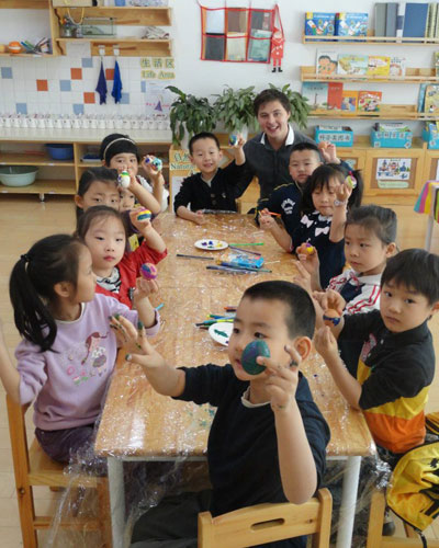 A group of young learners and a teacher at a table